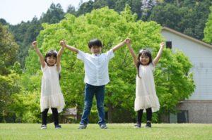 両手を挙げる3人の子供